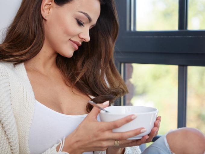 窓際でスープを飲む女性