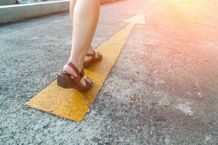 矢印に向って歩き出す女性の足もと画像
