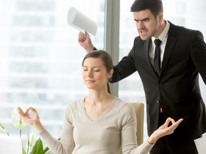 怒鳴りつける男性社員と瞑想のポーズをする女性