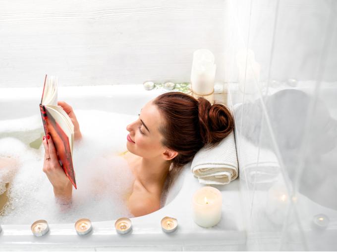 湯船に浸かりながら本を読む女性
