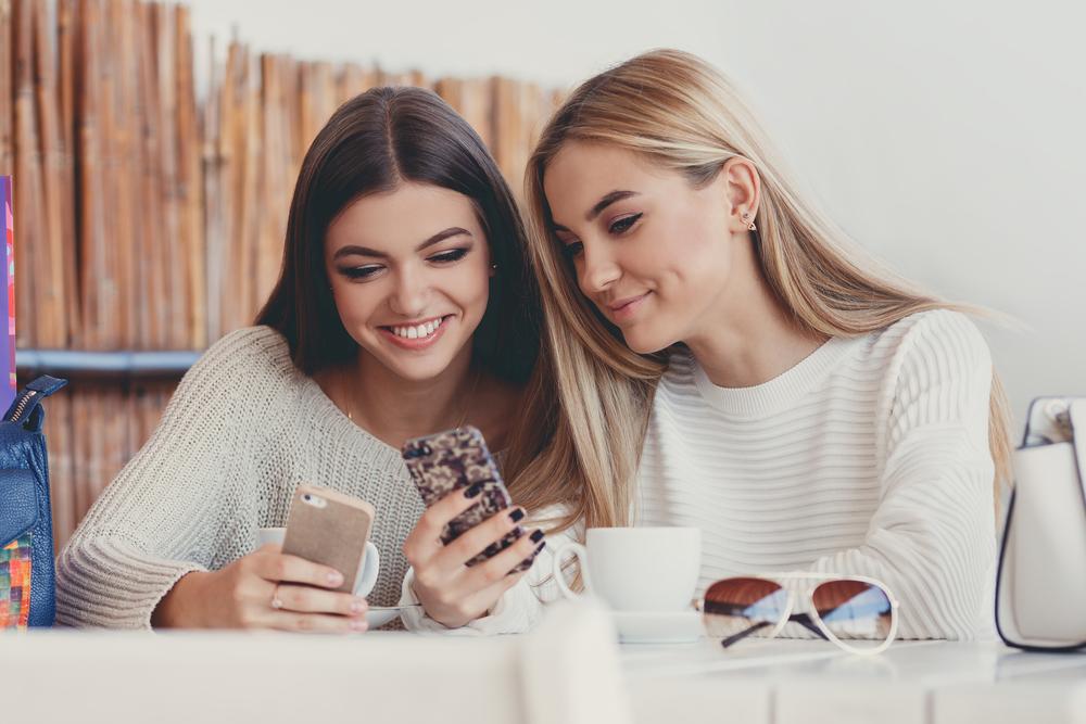 カフェでスマホを見ている女性2人