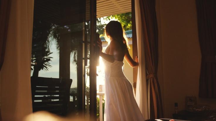 窓辺で朝日を浴びている女性