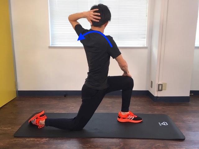 左ひざの外側に右手をあて、左手を後頭部にあて体を左方向へねじる