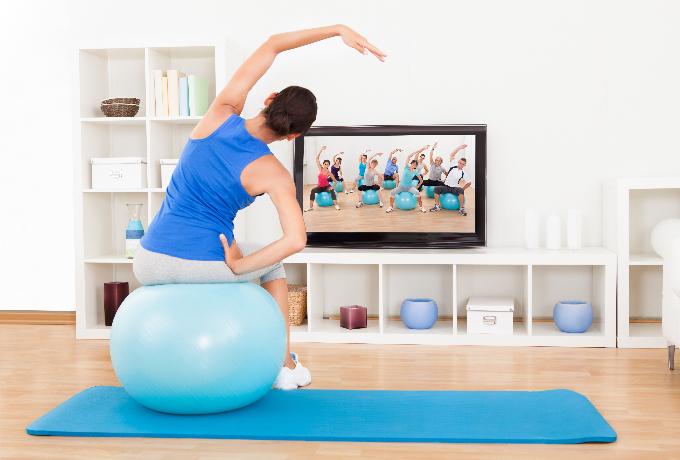 動画を見ながら、バランスボールの体操をする女性
