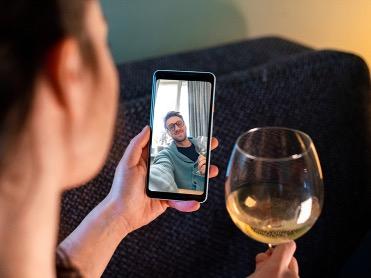 ケイタイの画面を通じて友人とお酒を飲む女性