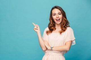 右手人差し指を立てる女性の画像