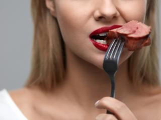 肉料理をフォークで口に運ぶ女性