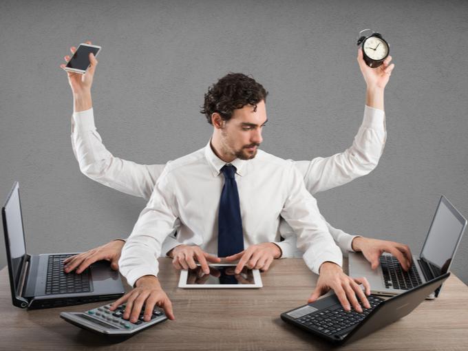複数の手でパソコンを操作し、マルチタスクをこなしている男性