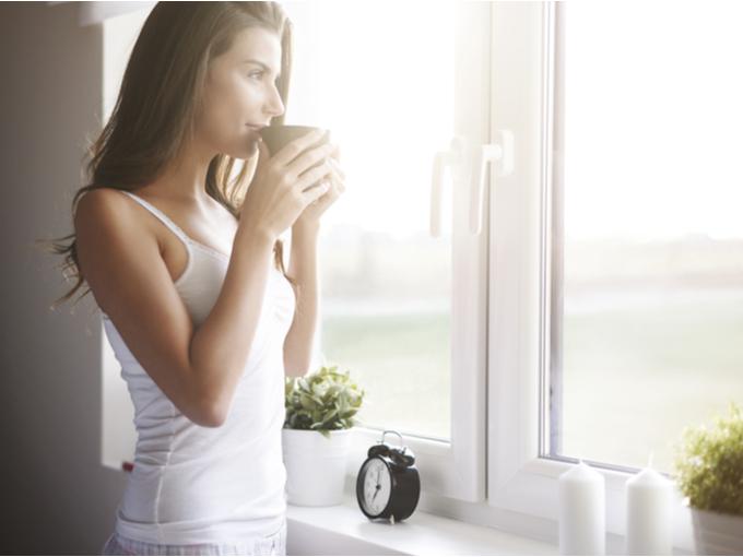 早朝に飲み物を飲みながらリラックスする女性