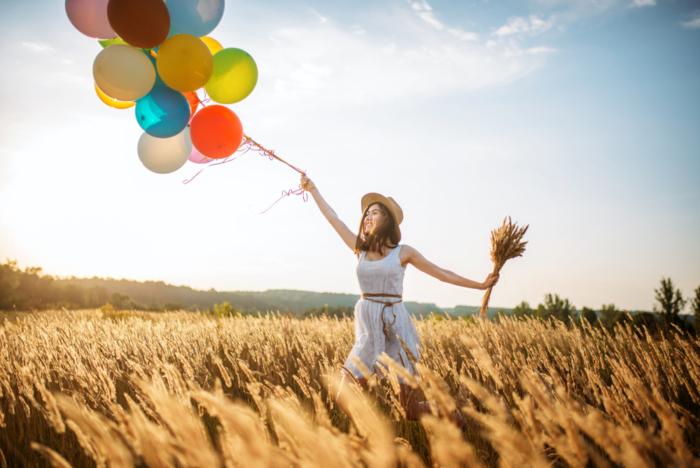 風船を飛ばそうとする女性の写真