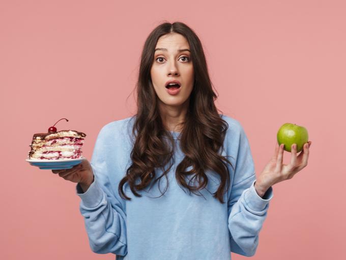 りんごとケーキを持って驚いた顔の女性