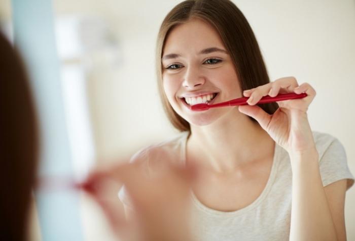 歯ブラシを歯に当てる女性画像