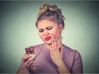 チョコレートを食べながら虫歯を気にする女性
