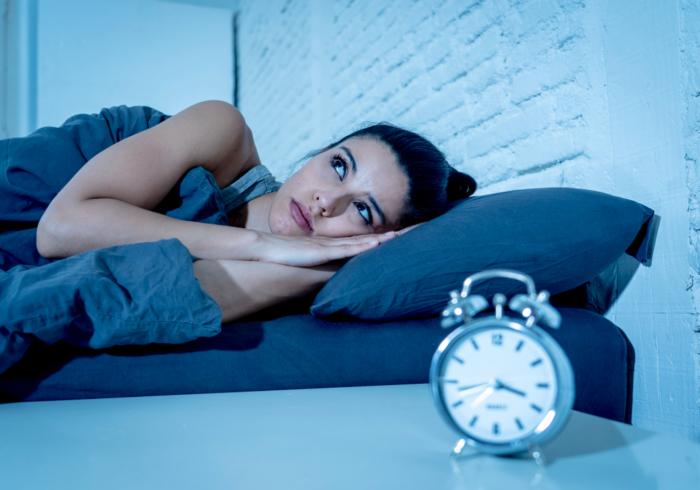 ベッドに入ってなかなか寝付けないでいる女性