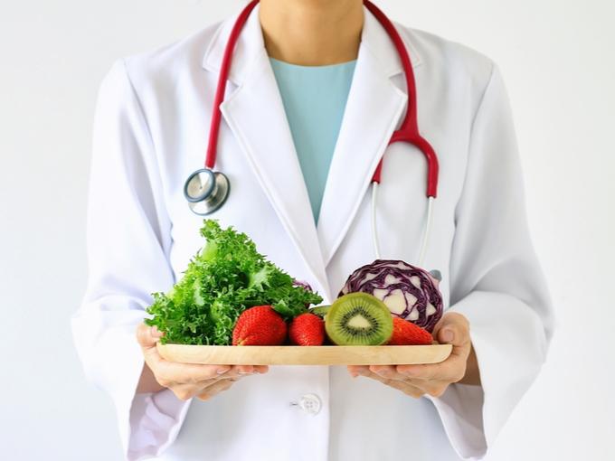 野菜やフルーツがのったトレーをもつドクター