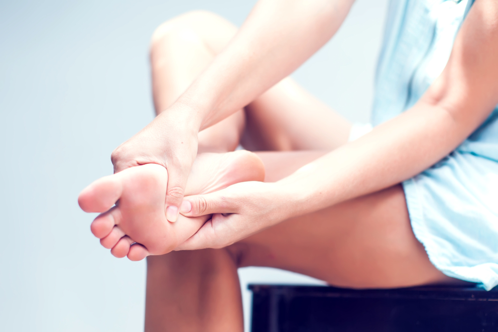 足裏を指でおしている女性