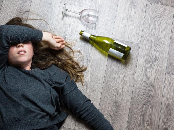 飲酒して眠る女性とお酒の瓶、グラス
