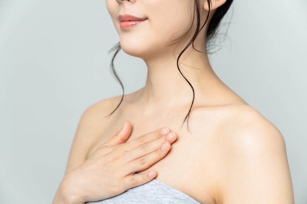 胸元を押さえる女性の画像