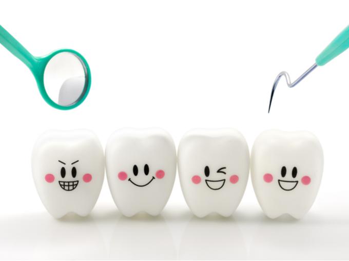 笑顔の表情をした歯のオブジェと歯の治療道具