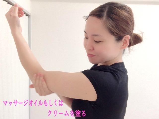二の腕にマッサージオイルもしくはクリームを塗る