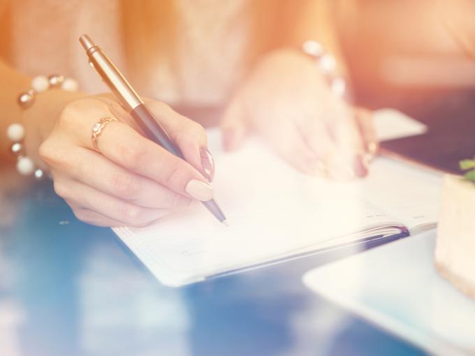1日のタスクの優先順位をノートに書き込む女性の手