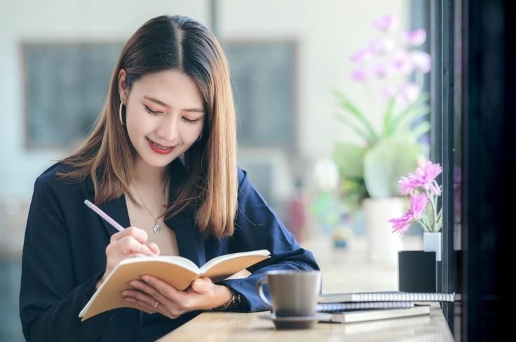 ノートに何かを書いている女性の画像