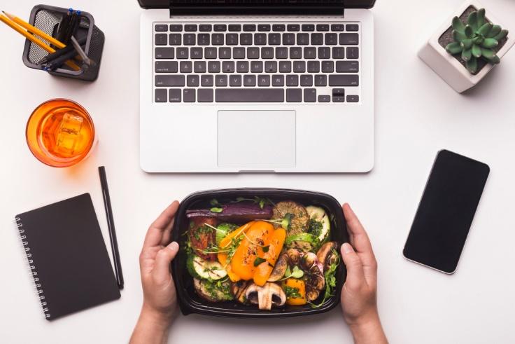 パソコンの前で弁当を広げる画像