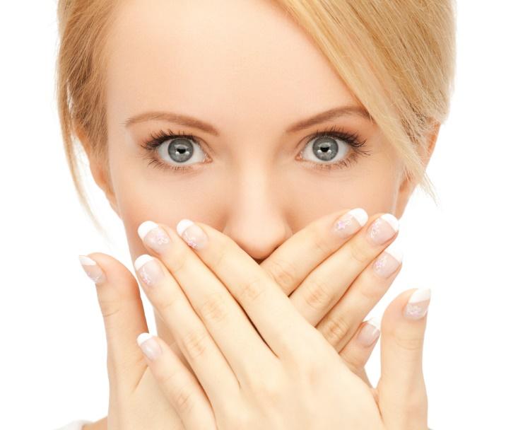 口元を両手で覆う女性の顔画像