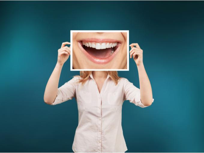 キレイな歯の口元の写真を顔の前にもつ女性