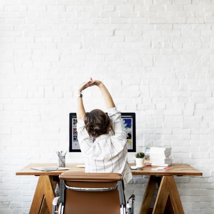 机に向かい、伸びをしている女性の背中画像