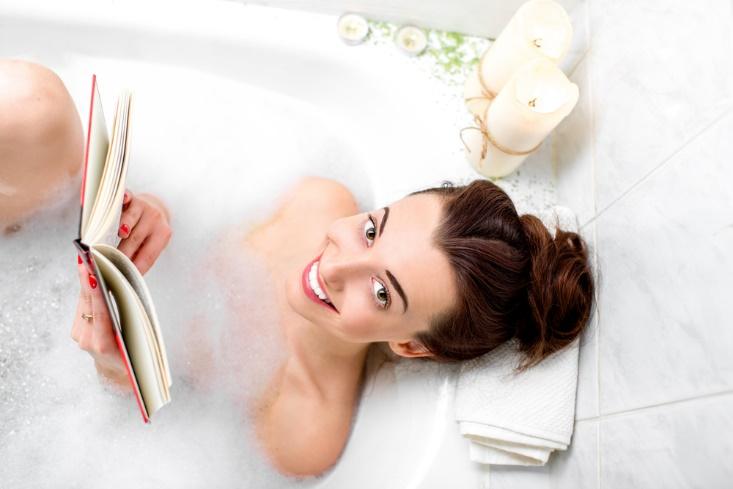 浴槽から顔を上げてほほ笑む女性の画像