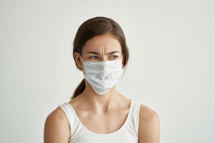 マスクをして顔をしかめる女性画像