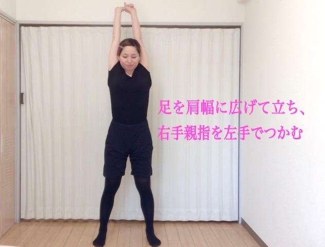 脚を肩幅に広げて立ち、右手の親指を左手でつかみながら腕を伸ばす
