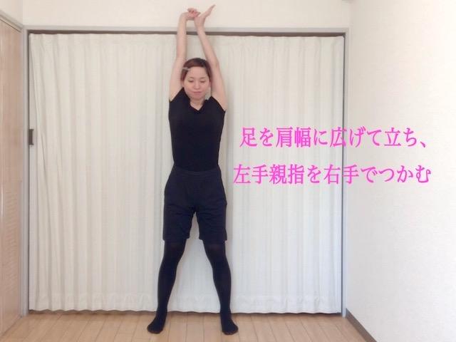 脚を肩幅に広げて立ち、左手の親指を右手でつかみながら腕を伸ばす
