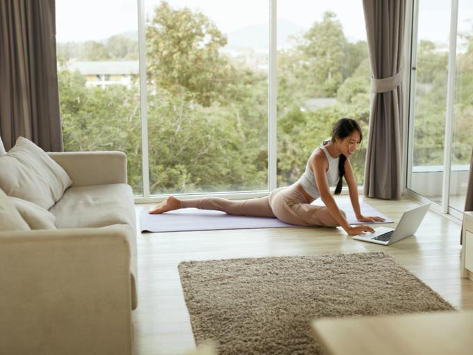 ストレッチ動画を見ながら体をほぐす女性