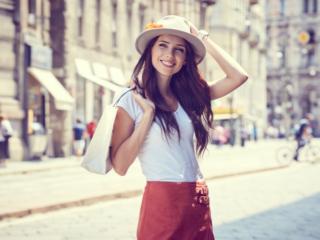帽子をかぶって街中を歩く女性