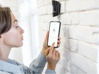 携帯から自宅のセキュリティーをチェックする女性