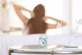 朝起きて朝日を浴びている女性の後ろ姿