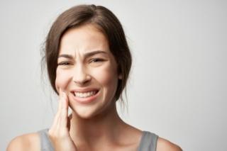 痛そうに頬を抑える女性の画像