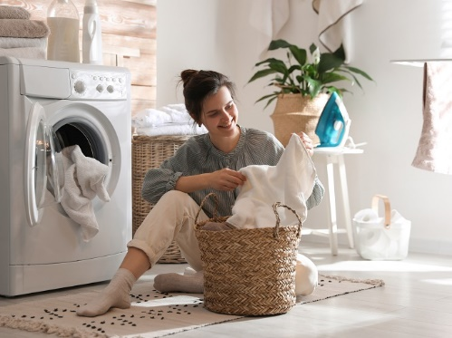 部屋の中で洗濯ものをもっている女性