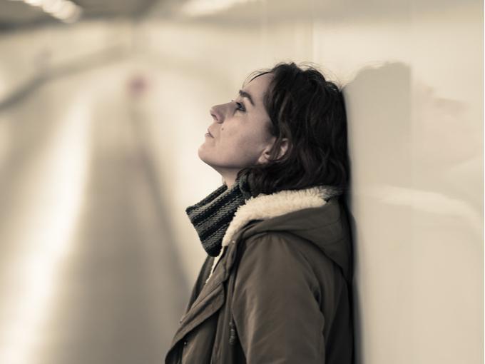 壁にもたれてもの思いにふける女性