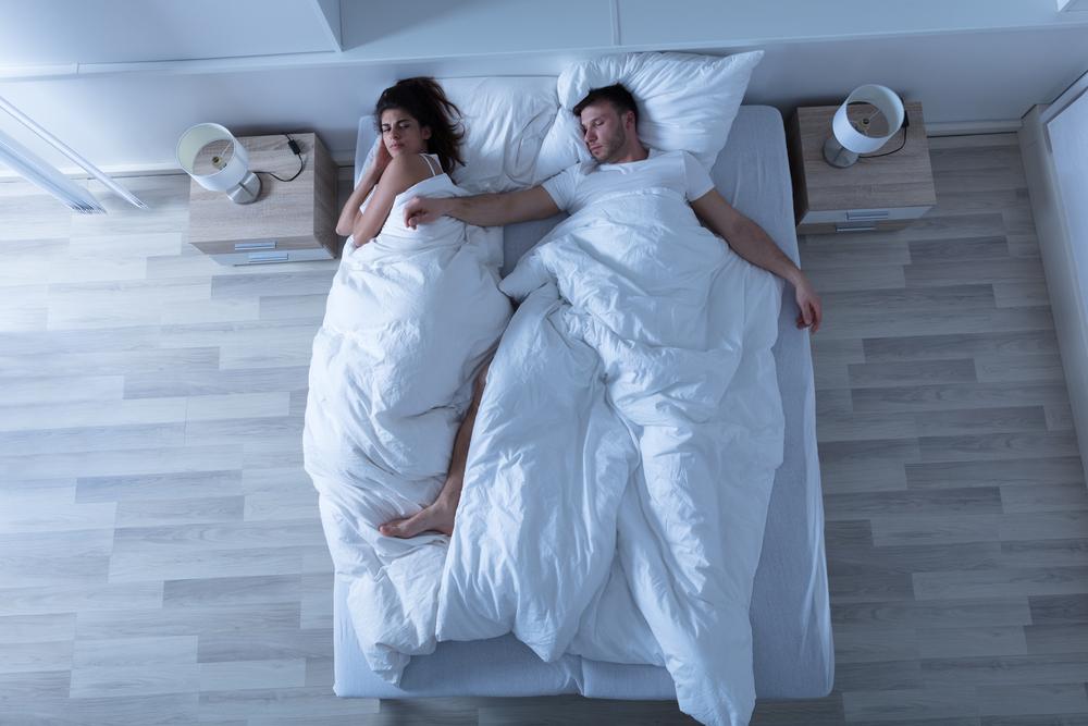 男性が寝相が悪く寝づらそうにする女性