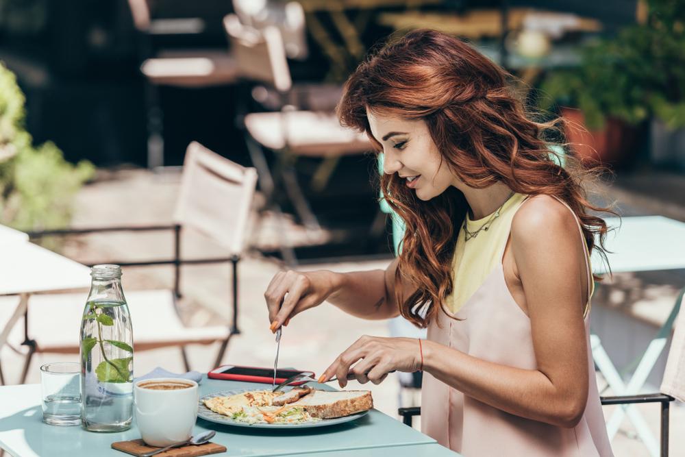 テラスでひとり食事を楽しむ女性
