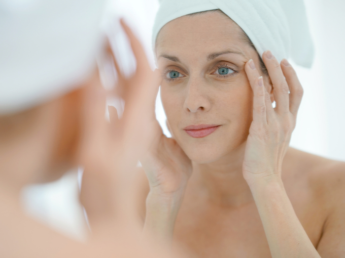 鏡で顔のシワを確認する女性