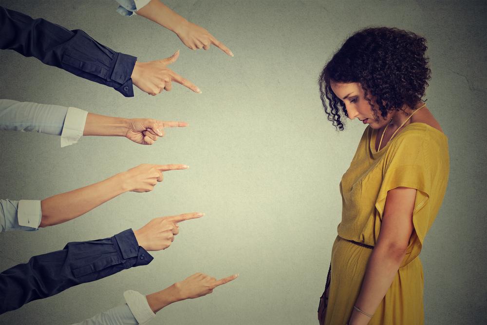 指をさされてしょんぼりしている女性の写真