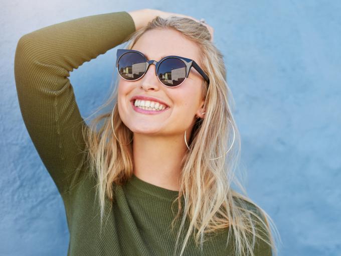 日差しを浴びながら笑顔を見せるサングラスの女性