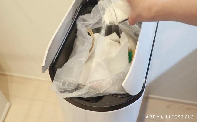 ゴミ箱に消臭剤をふりかけている画像