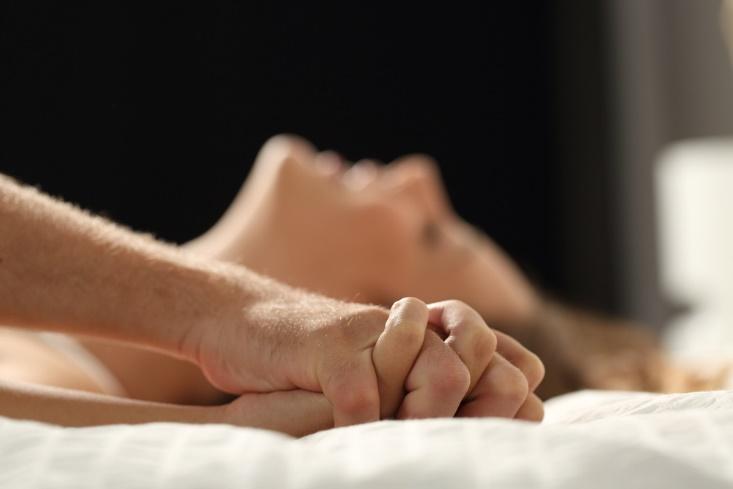 ベッドの上で手を合わせるカップル
