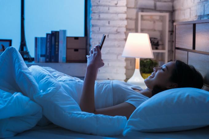 ベッドで夜遅くまでスマホをいじっている女性