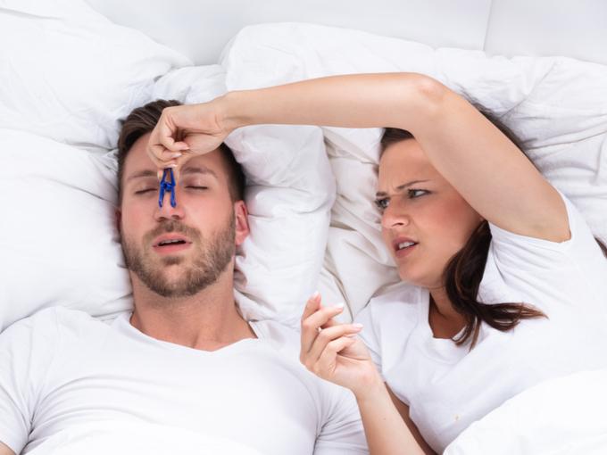 いびきをかく男性の鼻を洗濯ばさみでつまむ女性